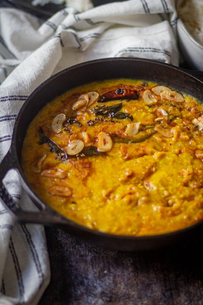 Moong dal in a black kadai with tempering of garlic