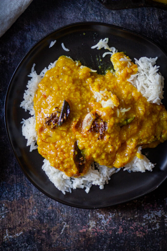 served moong dal tadka fry over rice on a black plate
